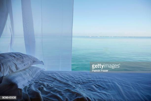 Tranquil tropical scene of a white sheets on luxurious bed and curtain with the ocean in the background