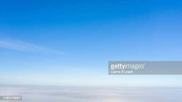 tranquil view just above low level morning fog. gentle blue with a little wisp of cloud higher up. - lianne loach stock pictures, royalty-free photos & images