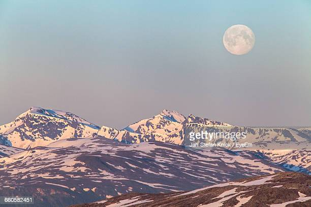 tranquil view of snowcapped mountains against moon in sky - jour photos et images de collection
