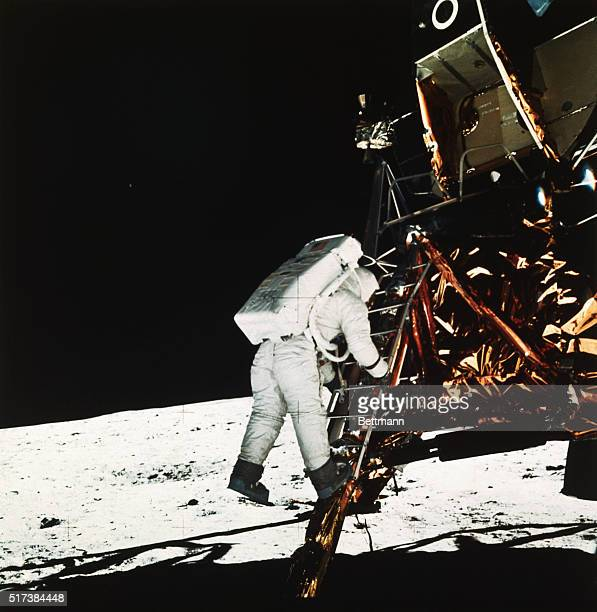 Tranquility Base or The Moon is shown with Buzz Aldrin pilot of the Apollo 11 Lunar Module as he descends steps of the LM ladder preparing to walk on...