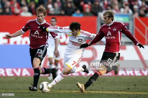 Tranquillo Barnetta of Leverkusen is challenged by Andreas Ottl and Marcel Risse of Nuernberg during the Bundesliga match between 1 FC Nuernberg and...