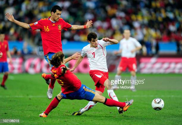 Tranquillo Barnetta of Switzerland comes under pressure from Carles Puyol of Spain during the 2010 FIFA World Cup South Africa Group H match between...