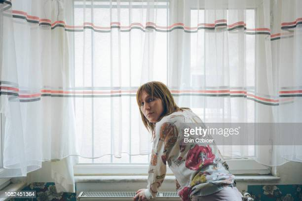 Trans woman leaning on a table by the window