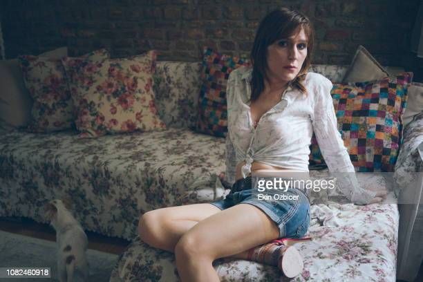 Young trans woman sitting on colorful couch
