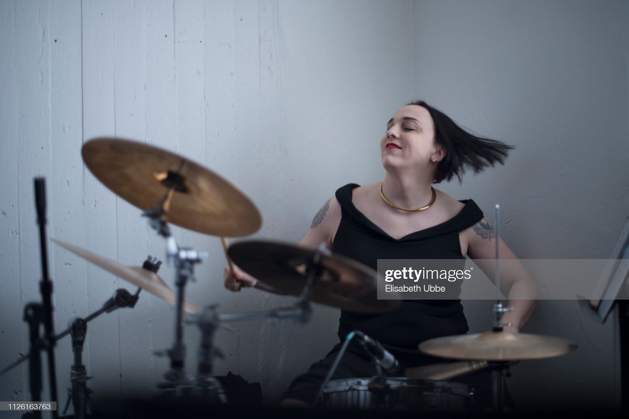 Trans woman playing drums : Stock Photo