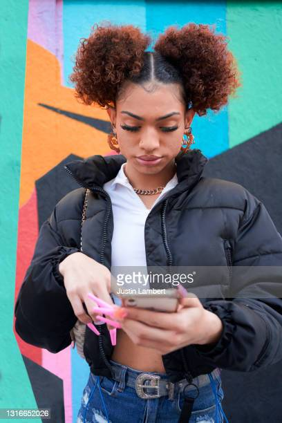 trans woman with long fingernails looking at her phone - human finger stock pictures, royalty-free photos & images
