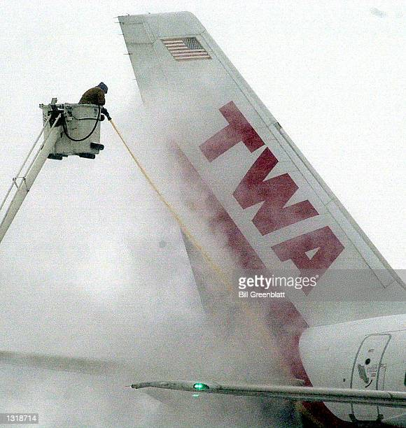 Trans World Airlines worker sprays deicing fluid on the tail section of a TWA plane shortly before takeoff December 13 2000 from LambertSt Louis...