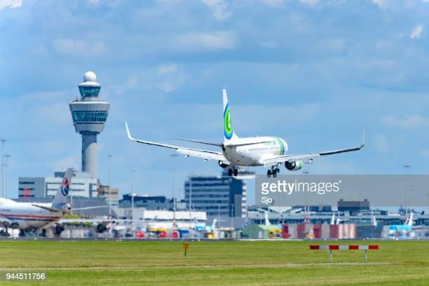 transavia boeing 737 airplane landing at schiphol airport - tower stock pictures, royalty-free photos & images