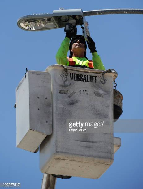 TransCore's Karl Korhonen replaces a street light with a new LED fixture August 1 2011 in Las Vegas Nevada The new energyefficient fixtures are...