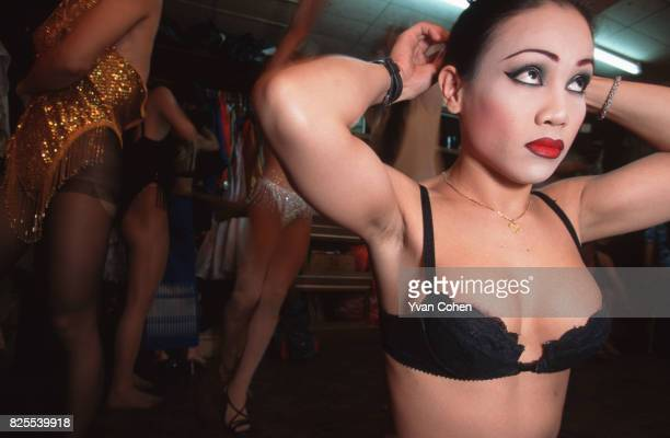 Transexuals and transvestites adjust their costumes backstage before a cabaret show at a nightclub in Soi 4 off Silom Road in downtown Bangkok...