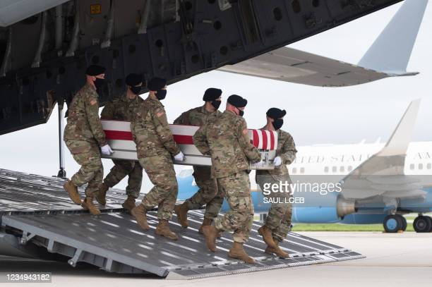 Transfer case with the remains of Army Staff Sgt. Ryan C. Knauss of Corryton, Tennessee, are carried off of a military aircraft as US President Joe...