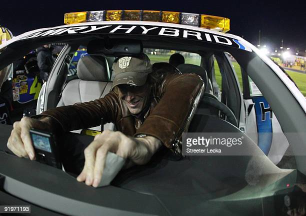 Transformers director Michael Bay tapes a camera to the dashboard of the pace car prior to driving it at the start of the NASCAR Sprint Cup Series...
