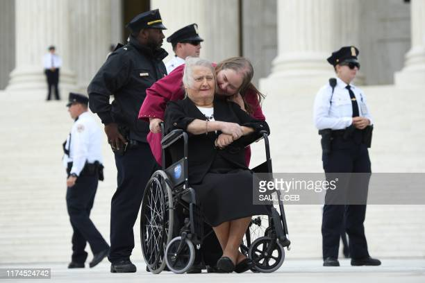 Transgender activist Aimee Stephenswith her wife on her shoulder sits in her wheelchair outside the US Supreme Court in Washington DC October 8 as...