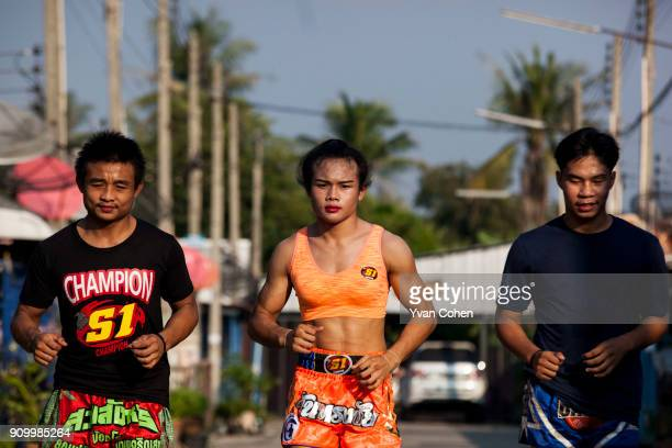 Transgender boxer Nong Rose out on a training run with her twin brother Somrak and other boxers close to the Ban Charoensuk Gym where she trains in...