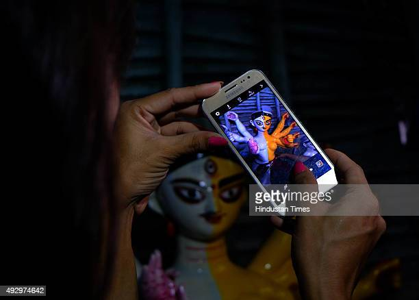 A transgender clicks a picture of the first 'Transgender' Durga idol of the country at the studio of artist China Pal at Kumartuli on October 16 2015...