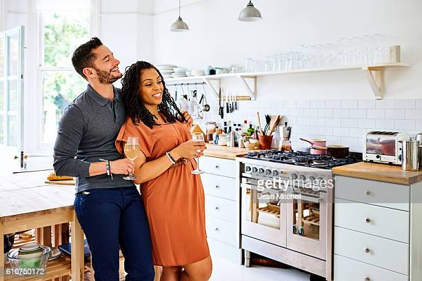 transgender couple having a glass of wine in kitchen - transgender man stock photos and pictures