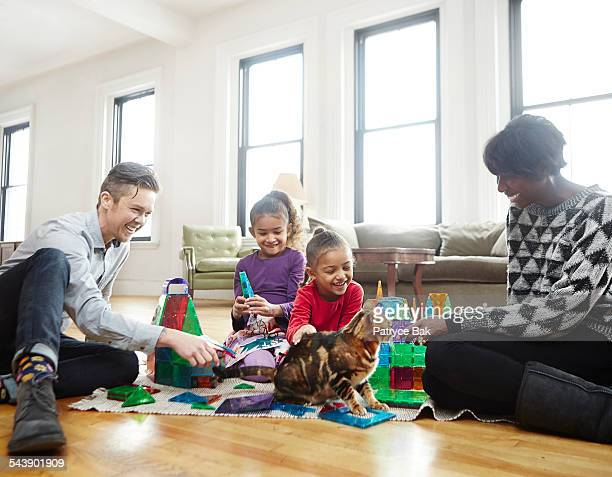 transgender dad plays w/ daughters in living room - leanincollection girls stock pictures, royalty-free photos & images