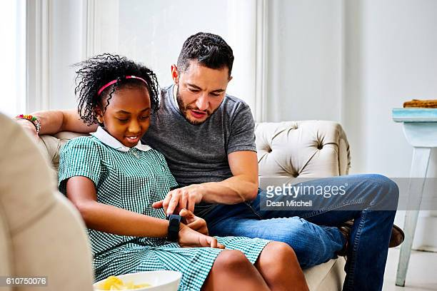 Transgender father with daughter using smart watch at home