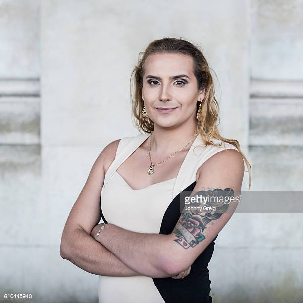 Transgender female with tattoo on arm looking towards camera