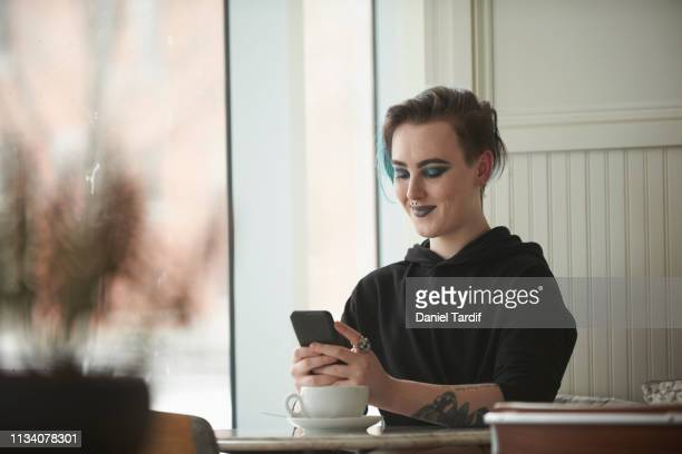 transgender male holding smart device in cafe. - gender fluid stock pictures, royalty-free photos & images