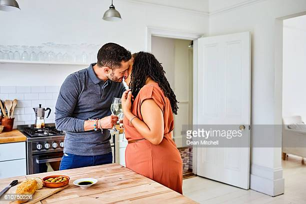 Transgender male kissing his wife in the kitchen