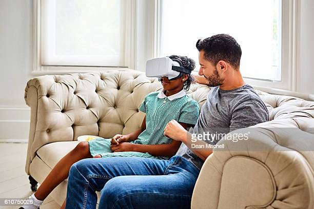 Transgender male with his daughter using VR glasses