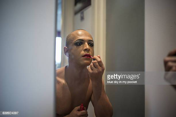 A transgender Man applying make up.