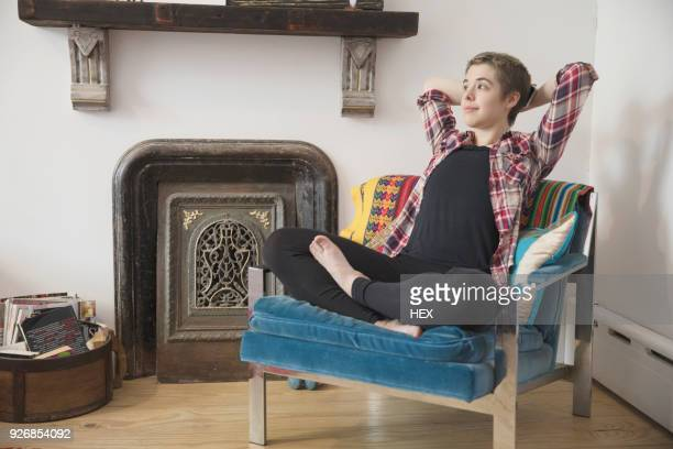 transgender person relaxing in their armchair - transgender man stock photos and pictures