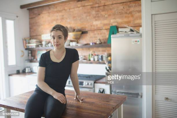 transgender person sitting on their kitchen counter - transgender man stock photos and pictures