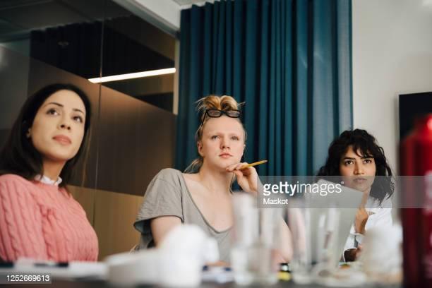 transgender professional sitting amidst businesswomen in board room during meeting - gender role fotografías e imágenes de stock