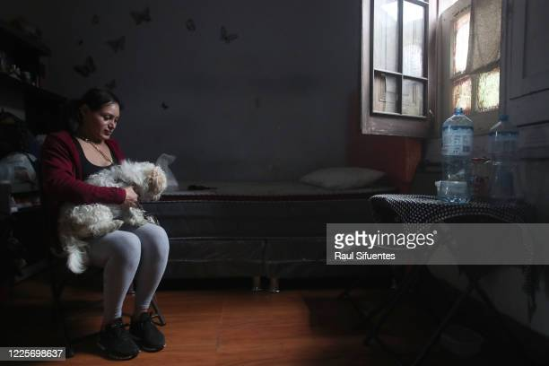Transgender sex worker Lizze carries her dog on her legs on July 8, 2020 in Lima, Peru. A group of 8 to 10 transgender sex workers share a house in...