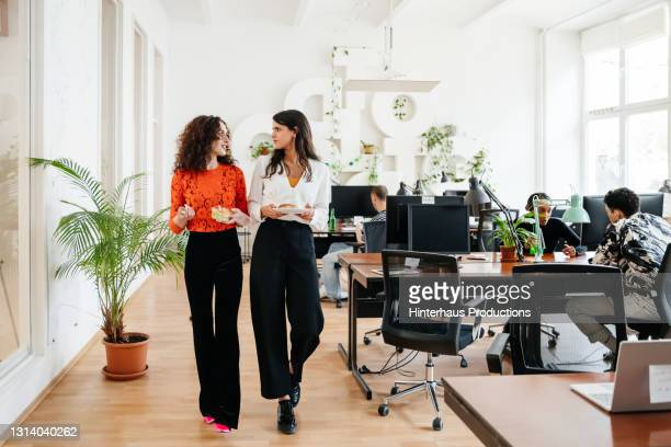 transgender woman heading for lunch with office colleague - business stock pictures, royalty-free photos & images
