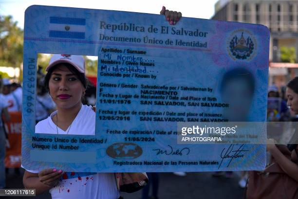 A transgender woman holds a sign simulating a personal identification asking for an identity law for transgender people during a demonstration as...