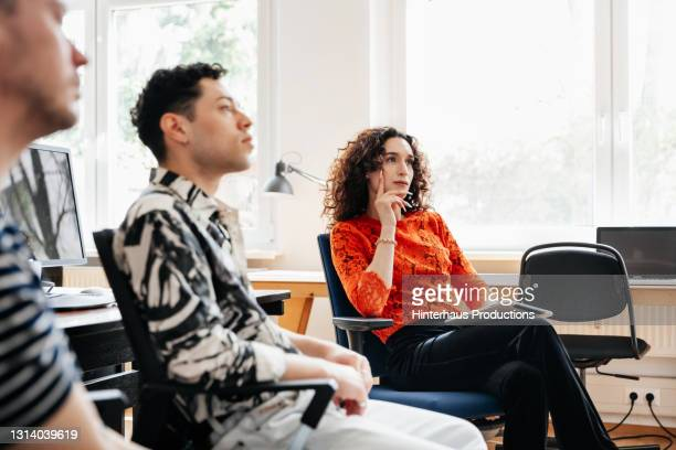 transgender woman listening during business meeting in office - germany stock pictures, royalty-free photos & images
