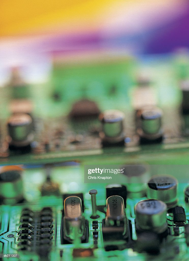 Transistors on a colorfully variegated circuit board : Stock Photo