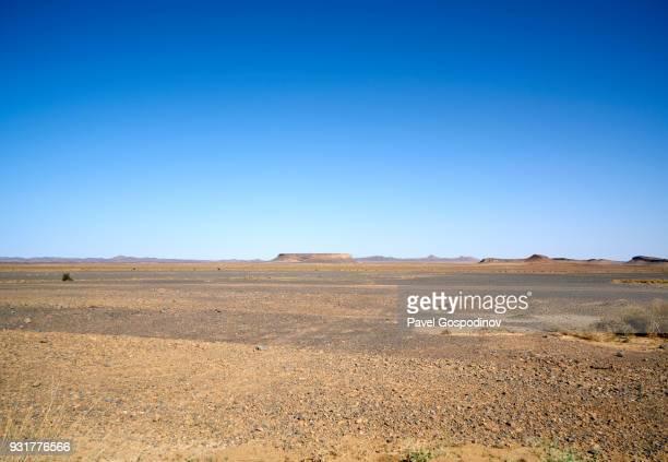 transition between a barren rocky desert, hamada, and sandy desert in moroccan sahara, morocco - 荒野 ストックフォトと画像