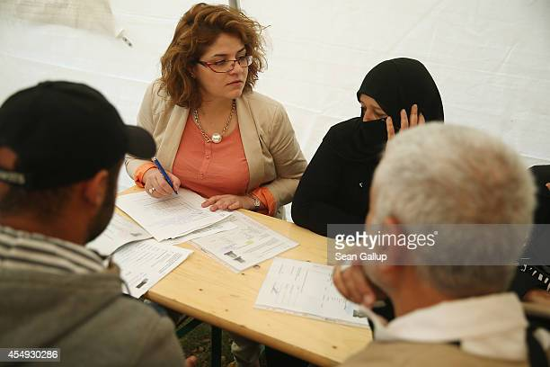 A translator helps a family from Syria fill out application forms for refugee status in a makeshift office in a tent outside the Berlin Central...