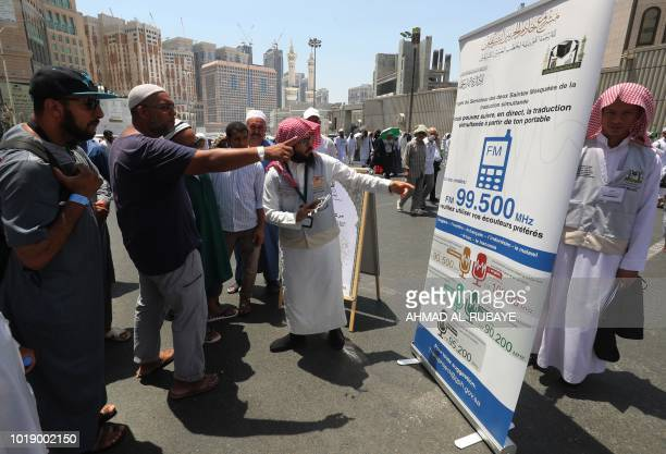 A translator helps pilgrims find information on a poster displaying helpful smartphone applications in the Saudi holy city of Mecca ahead of the...