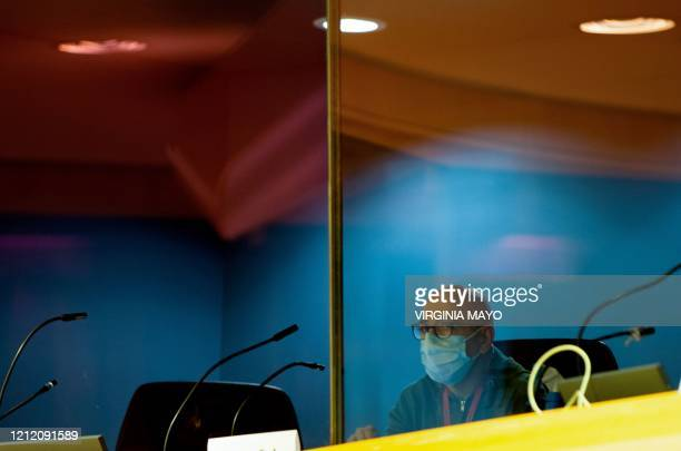 Translator wearing a protective face mask sits in his booth protected with a plastic panel, during a press conference of the Executive Vice President...