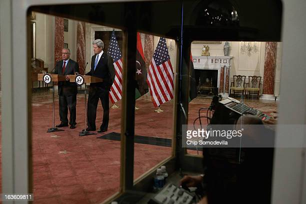 Translators work in a sound-proof booth as Libyan Prime Minister Ali Zeidan and U.S. Secretary of State John Kerry hold a news conference in between...