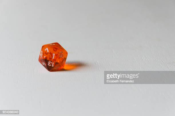 translucent orange twenty sided dice - gambling table stock pictures, royalty-free photos & images