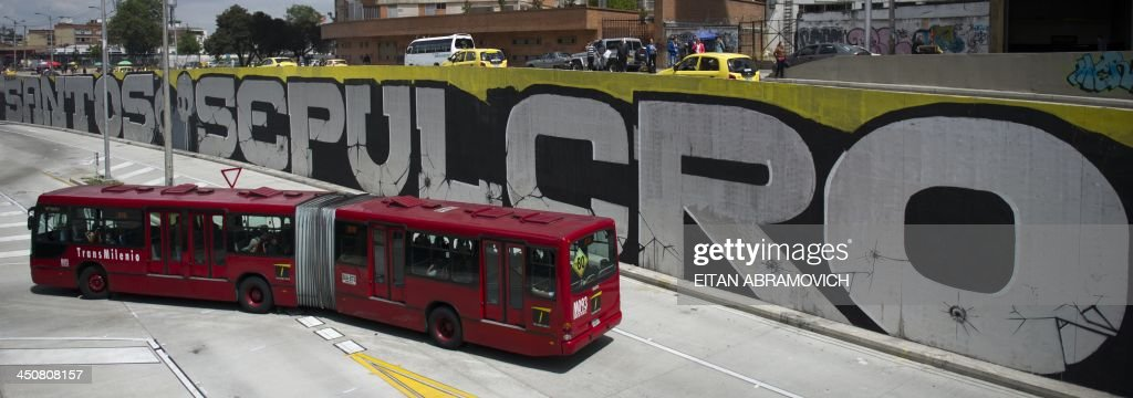 Transmilenio rapid bus drives by a graffiti in Bogota on November 19, 2013. The graffiti, once considered vandalism, is gaining more space in Bogota, with a city tour and the support of the mayor's office which provides walls, materials and fees to street artists. AFP PHOTO/Eitan Abramovich /
