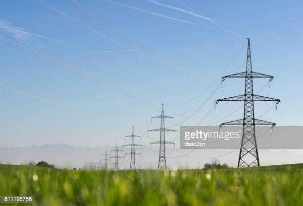 Transmission towers and overhead electrical power lines with mountain range, Bavaria, Germany