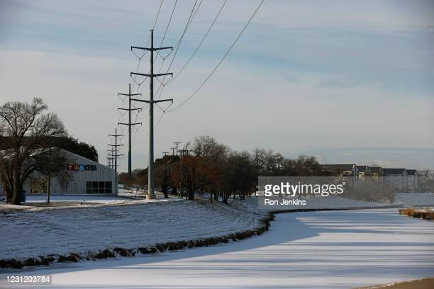 Transmission towers support power lines above the frozen over Clear Fork of the Trinity River after a snow storm on February 16, 2021 in Fort Worth,...