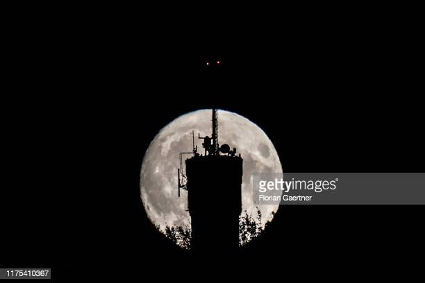 A transmitter mast on the hill 'Landeskrone' is pictured in front of the rising moon on October 12 2019 in Goerlitz Germany