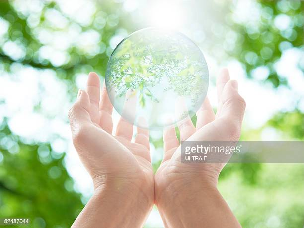 a transparent ball is floating over the palms.  - world kindness day fotografías e imágenes de stock