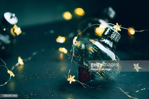 transparent christmas bauble with natural fir tree branch inside on dark green background with fairy lights. - ビーズ ストックフォトと画像