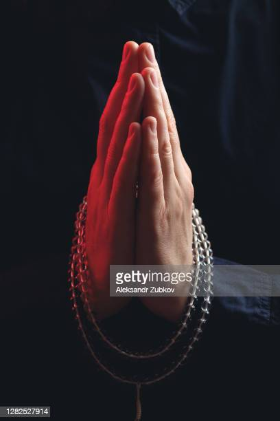 transparent crystal rosary in the hands of a young man, he is doing yoga. the guy's hands are folded in a prayer gesture namaste. religious symbol of the concept of faith, prayer, meditation and mantra repetition. - prayer pose greeting bildbanksfoton och bilder