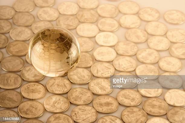 A transparent globe on scattered coins