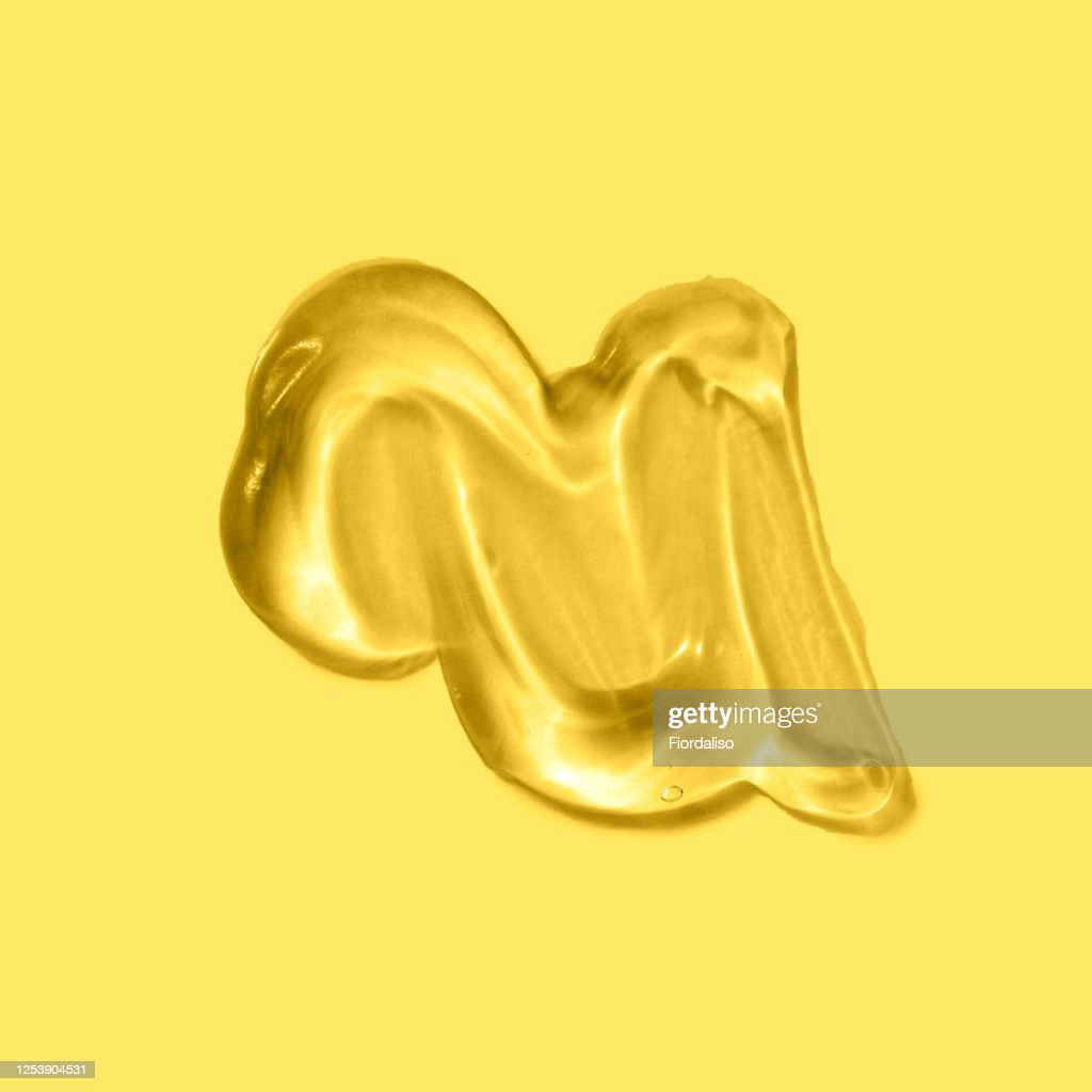 Transparent liquid gel on a yellow background : Stock Photo